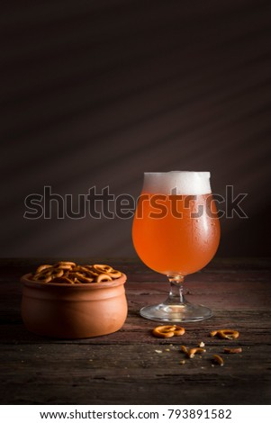 Glass of lager beer with pretzel snack on vintage wooden board on black background. Beer and snack Stock photo © DenisMArt