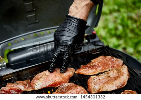 Grilled turkey meat. Hand of young man grilling some meat meat  Stock photo © Illia