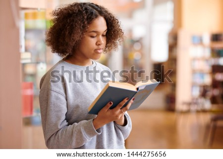 Wavy-haired multicultural girl in grey sweatshirt reading book of tales Stock photo © pressmaster