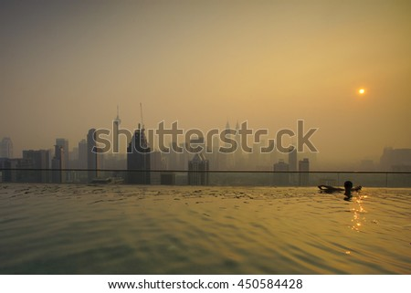 Man in outdoor swimming pool with city view in blue sky VERTICAL FORMAT for Instagram mobile story o Stock photo © galitskaya