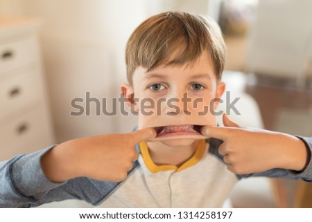 Close up of a mischievous boy stretching his mouth with his fingers at home Stock photo © wavebreak_media