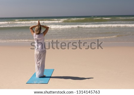 Rear view of senior woman meditating in prayer position on the beach with ocean in the background Stock photo © wavebreak_media