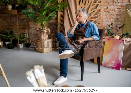 Pensive artist sitting in front of easel and looking at unfinished painting Stock photo © pressmaster