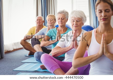 front view of active senior men performing yoga relaxing with ball exerciceat home stock photo © wavebreak_media