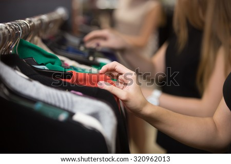 pretty girl looking through collection of casual dresses hanging on rack stock photo © pressmaster