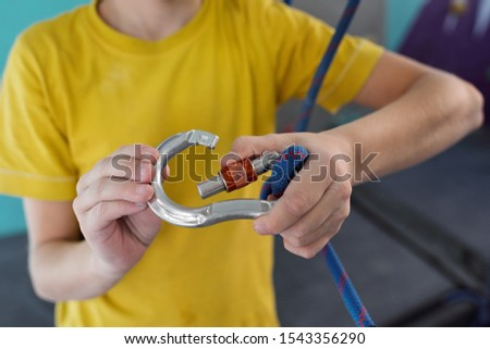 Active schoolboy locking carabiner with thick blue rope before training Stock photo © pressmaster