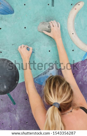 Back view of young blonde female climber grabbing small artificial rocks Stock photo © pressmaster