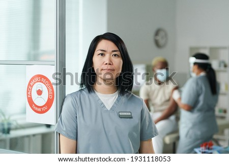 Confident clinician in uniform standing in front of camera while using touchpad Stock photo © pressmaster