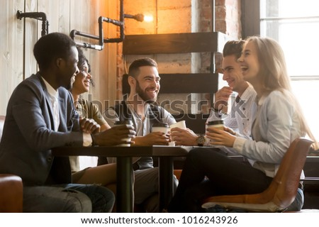 Group of happy casual college friends sitting by table in cafe after classes Stock photo © pressmaster