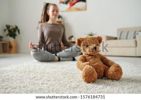 Soft brown teddybear sitting on carpet on background of young active woman Stock photo © pressmaster