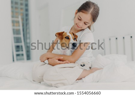 Photo of relaxed beautiful small girl plays with pedigree dog, embraces favourite animal, dressed in Stock photo © vkstudio