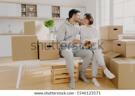 Lovely spouses sit near carton big boxes, drink coffee and talk about future plans, relocate in new  Stock photo © vkstudio