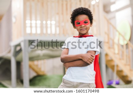 Cute African little boy in white casualwear and red mantle of superman Stock photo © pressmaster