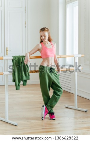 Beautiful fit ginger female dancer has rest near barre in ballet dancing studio, focused down with t Stock photo © vkstudio