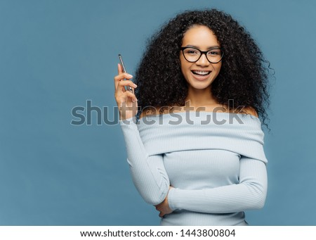 Waist up shot of mirthful Afro American woman holds smart phone, waits for call, enjoys pleasant con Stock photo © vkstudio