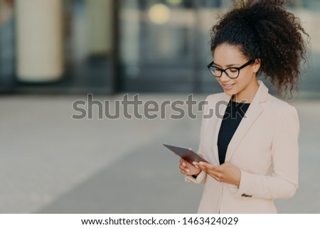 Prosperous owner of business company stands with digital touchpad, focused in screen, searches for n Stock photo © vkstudio
