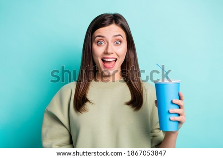 Photo of young surprised woman drinking soda from plastic bottle Stock photo © deandrobot