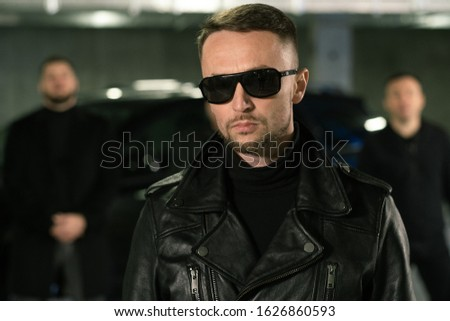 Bearded criminal authority in sunglasses, black leather jacket and jeans Stock photo © pressmaster