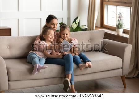 Twee weinig aanbiddelijk zusters zitten sofa Stockfoto © vkstudio
