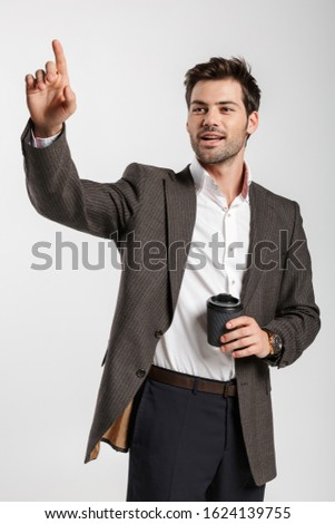 Image of pleased businessman drinking coffee and pointing finger upward Stock photo © deandrobot