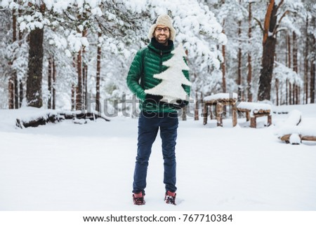 Portrait of man with thick beard and musatche has pleased expression, walks in beautiful winter fore Stock photo © vkstudio