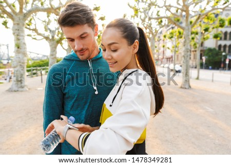 Image of young unshaven sportsman using smartwatch and earphones Stock photo © deandrobot