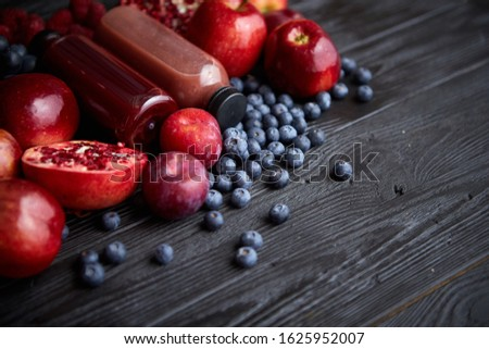 Various fresh red, purple black fruits. Mix of fruits and bottled juices on black Stock photo © dash
