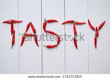 A word TASTY formed with small red chilli peppers. Placed on white wooden table Stock photo © dash