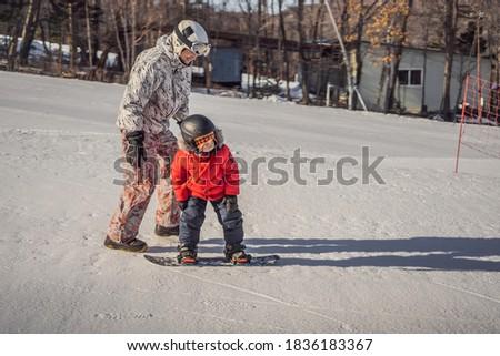 Dad teaches son snowboarding. Activities for children in winter. Children's winter sport. Lifestyle Stock photo © galitskaya