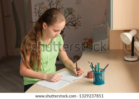 Stock photo: Beautiful young school girl left-handed working at home in her room with a laptop and class notes st