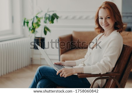 Sideways shot of redhead young Caucasian woman freelancer makes remote work, concentrated in laptop  Stock photo © vkstudio