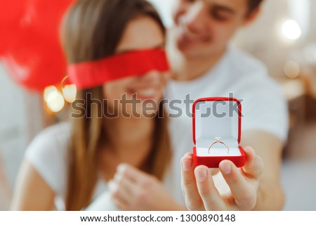 Happy young hispanic man gifting a ring to a beautiful surprised Stock photo © HASLOO
