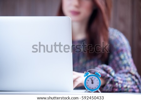 beautiful young woman typing text on keyboard near alarm clock o Stock photo © Massonforstock