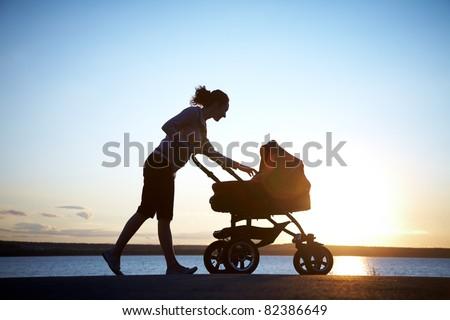 Silhouette of mother with stroller enjoying motherhood at sunset Stock photo © blasbike