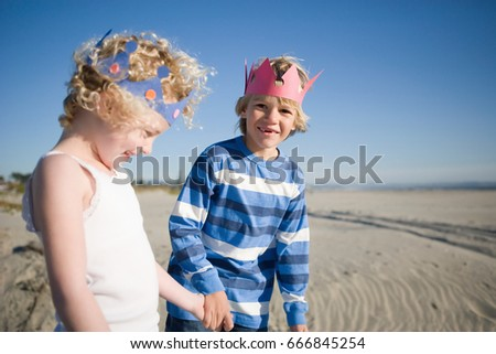 brother and sister wearing paper crowns holding hands stock photo © is2
