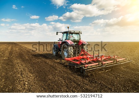 Farmer in tractor preparing land with seedbed cultivator against the blue sky Stock photo © artjazz