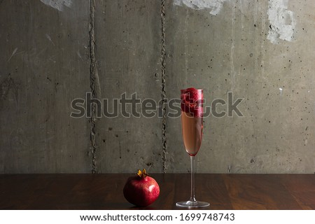 Elegant glass of pink rose champagne with raspberry on stick with fresh berries and mint leaf on bla Stock photo © DenisMArt