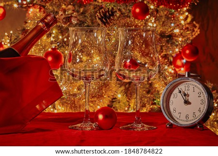 Stock photo: Two champagne glasses against holiday lights and clock at midnig
