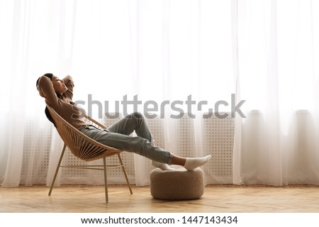 Young woman at home sitting on modern chair near window relaxing in living room stock photo © ruslanshramko