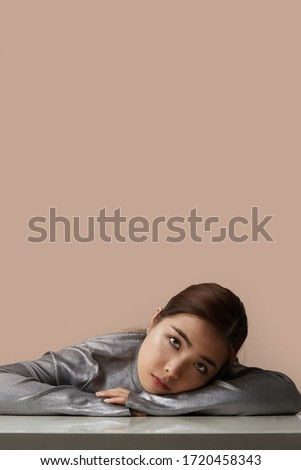 Beautiful asian woman posing isolated over beige wall background showing display of phone. Stock photo © deandrobot