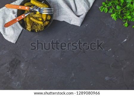 Pickled gherkins or cucumbers in bowl on back concrete surface Stock photo © artsvitlyna