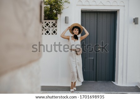 Stylish woman in fashionable beige dress standing near leather bag. Stock photo © studiolucky