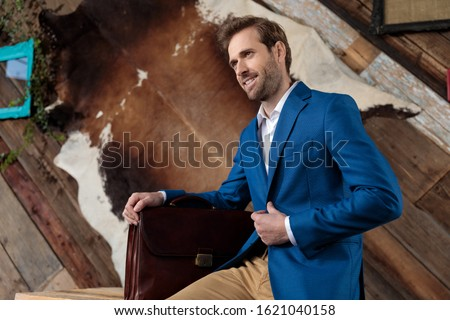 smiling young casual man holding briefcase and adjusts his colla stock photo © feedough