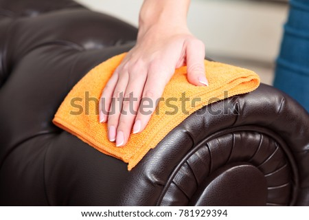 Closeup shot of female hand wiping brown leather chester couch o Stock photo © Nobilior
