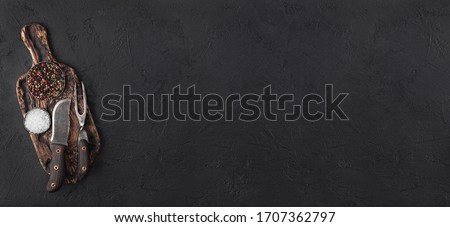 Stock photo: Vintage meat knife hatchet on vintage chopping board and black stone table background. Butcher utens