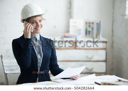 Smiling Female Contractor In Hard Hat Using Smart Phone At Const Stock photo © feverpitch