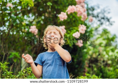 Little boy sneeze in the park against the background of a flowering tree. Allergy to pollen concept Stock photo © galitskaya