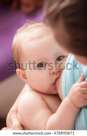 mother is breastfeeding a baby sitting on a chair close to the window stock photo © lopolo