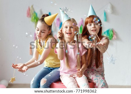 Group of cheerful little kids in birthday caps sitting in circle on rug Stock photo © pressmaster