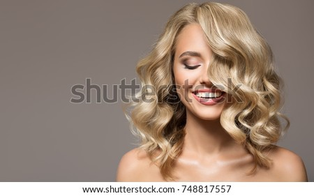 Young beautiful woman with blonde curly hair on grey background Stock photo © dashapetrenko